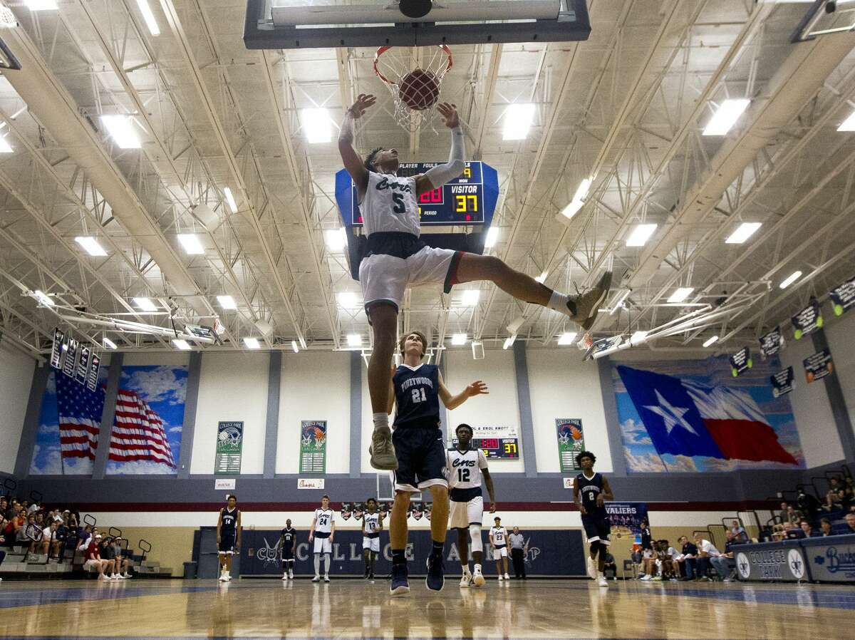College Park guard Quentin Grimes (5) dunks the ball past Pineywoods Academy guard Daniel Thurman (21) during the second quarter of a non-district high school boys basketball game at College Park High School, Thursday, Dec. 21, 2017, in The Woodlands.