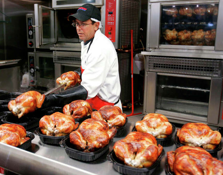 In this May 8, 2008, file photo, a butcher spreads out rotisserie-roasted chicken at Costco in Mountain View, Calif. There are shortcuts you can take at the supermarket that will help you get dinner on the table faster throughout the week. They range from choosing vegetables that are already prepped or frozen to taking home the occasional rotisserie chicken to buying bulk. Photo: AP Photo/Paul Sakuma, File