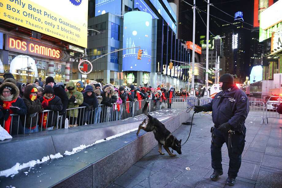 A police K-9 unit patrols last year's crowd that had gathered in New York City's Times Square for the New Year's Eve celebration. About 7,000 police officers will be on duty this year. Photo: Go Nakamura / Associated Press 2017