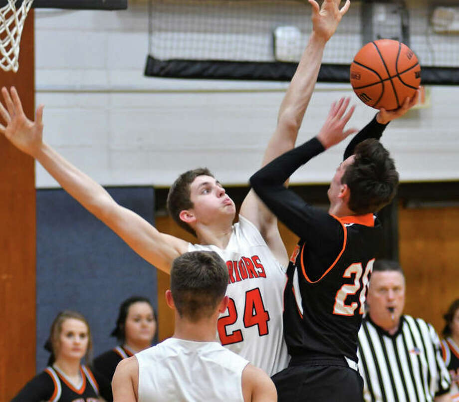 Calhoun's Ben Eberlin (24) contests a shot by Hillsoboro's Keaton Pruett during the championship game of the Carlinville Tournament on Saturday night in Carlinville. Photo: Bonnie Snyders / For The Telegraph