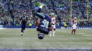 Seattle Seahawks' Tyler Lockett (16) flips his way into the end zone on a 29-yard touchdown reception against the Arizona Cardinals during the first half of an NFL football game, Sunday, Dec. 30, 2018, in Seattle. (AP Photo/John Froschauer)