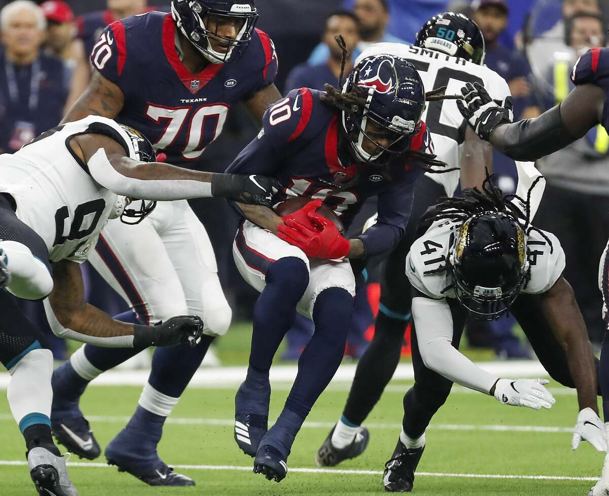 Houston Texans wide receiver DeAndre Hopkins (10) is hit by Jacksonville Jaguars cornerback Tre Herndon (41) as makes a catch in traffic during the first quarter of an NFL football game at NRG Stadium on Sunday, Dec. 30, 2018, in Houston.