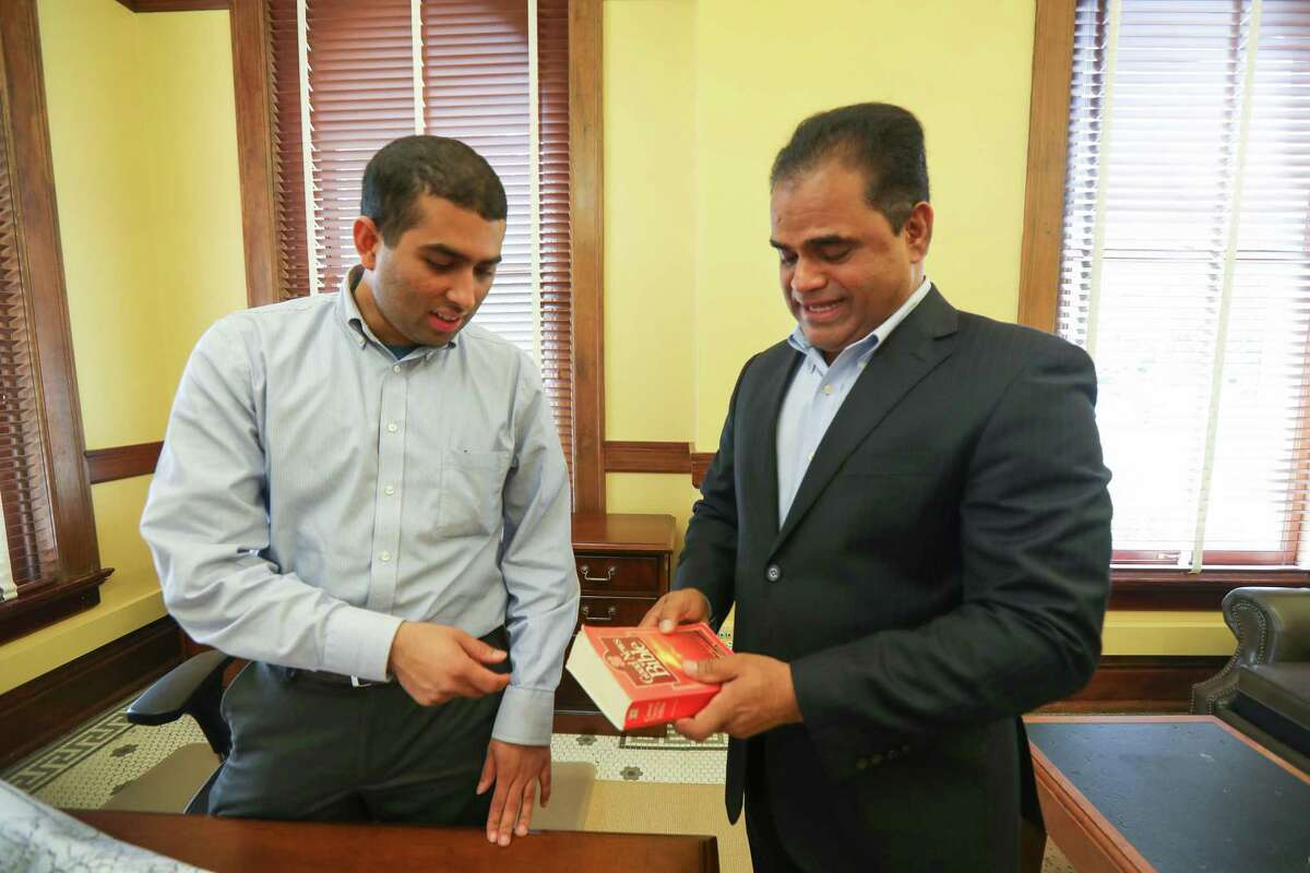 Taral Pate (left) looks at a Bible that Fort Bend's newly elected County Judge, K.P. George, unpacked in his office Friday, Dec. 28, 2018, in Richmond. George explained that he carried the book with him since he immigrated from South India over 25 years ago.