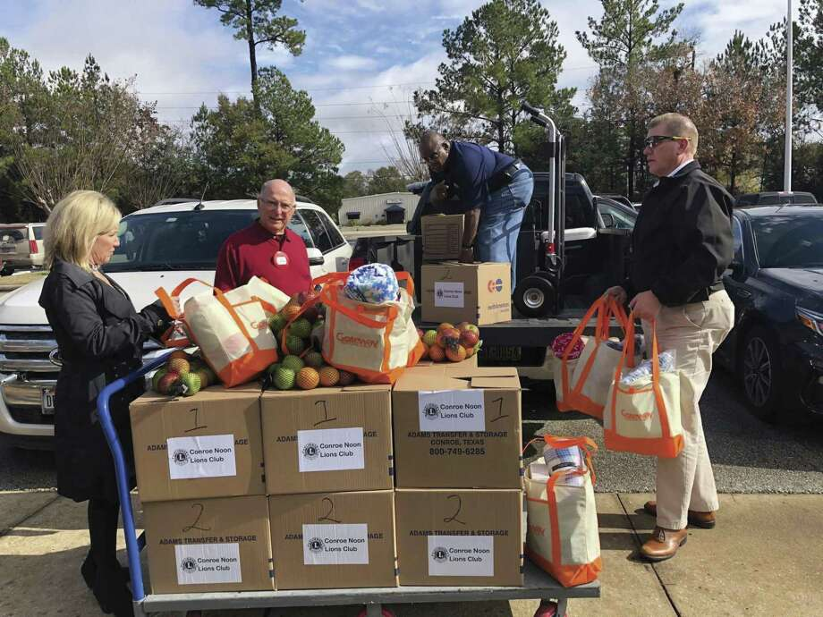 Members of the Conroe Noon Lions Club load Christmas Baskets which were delivered to 34 elderly and shut-in families full of food, supplies and toiletry items. Pictured from left are Mona Hamby, Don Schroeder, Roosevelt Lasker, Eddie Davis.