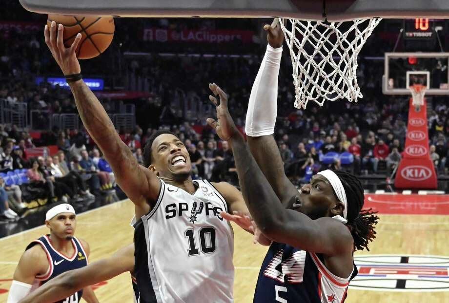 Spurs guard DeMar DeRozan shoots over Clippers forward Montrezl Harrell on Saturday, when DeRozan had 25 points and 13 rebounds in the Spurs' 122-111 victory. Photo: Mark J. Terrill / Associated Press / Copyright 2018 The Associated Press. All rights reserved.