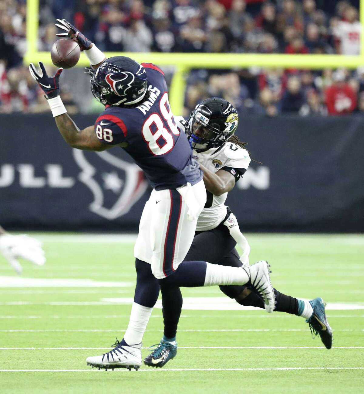 Houston Texans tight end Jordan Akins (88) tries to catch a pass against Jacksonville Jaguars defensive back Jarrod Wilson (26) during the fourth quarter of an NFL football game at NRG Stadium, Sunday, Dec. 30, 2018, in Houston.