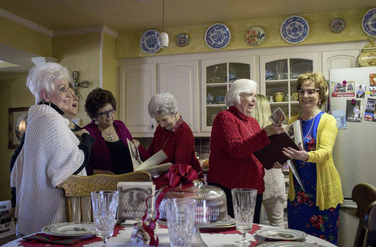 Anniece Larkins, from left, Pat Thomas, Gloria Floyd, Gwen Gerlich, Charlotte Sterling, and Wanda McKay, look through picture albums from their youth, at the home of Joyce Willoughby.