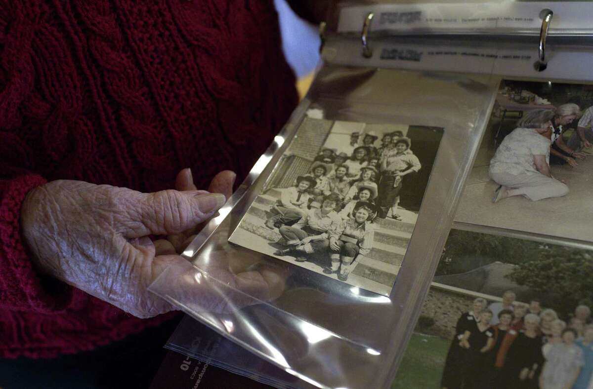 """Charlotte Sterling, 77, looks at an old photo of herself and her childhood friends, group known as the """"Lucky 13."""""""