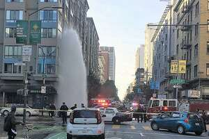 A fire hydrant spews water skyward in San Francisco's Tenderloin district after a suspect crashed a stolen Toyota Corolla into it on Sunday, Dec. 30, 2018. Two suspects, both fugitives, were arrested. The incident caused traffic problems for hours in the area.