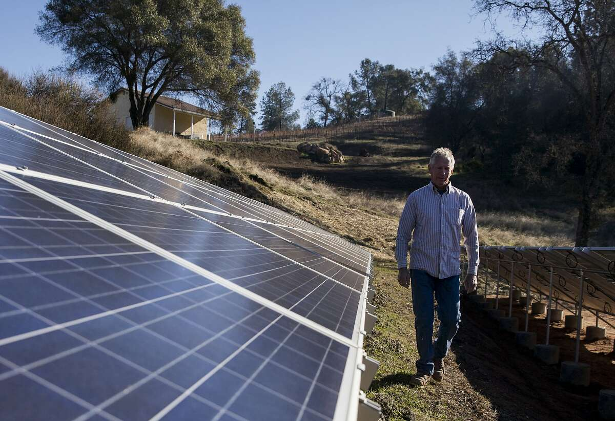 Contractor Kirk Reuter walks through solar panels he recently installed on the property of La Mesa Vineyards in Plymouth, Calif. Saturday, Dec. 29, 2018.