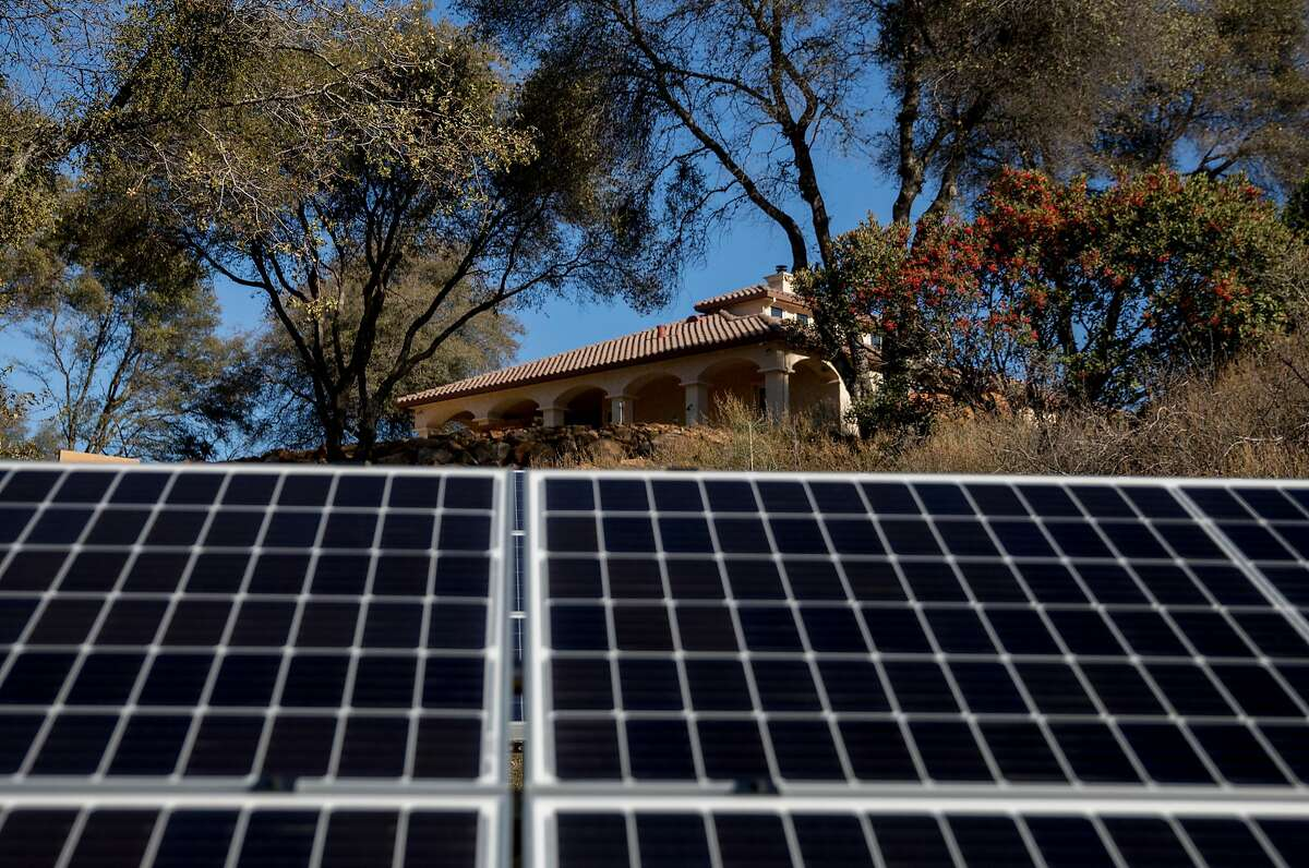 The home of vineyard owner Come Lague peeks out above newly-installed solar panels at La Mesa Vineyards in Plymouth, Calif. Saturday, Dec. 29, 2018.