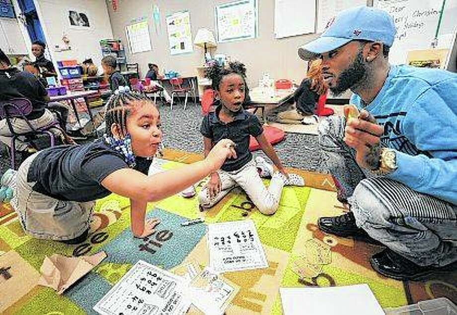 Parent mentor Darius Slaw helps first graders Kimorah Allston and Eunique Willingham with a math lesson at French Academy in Decatur. The statewide Parent Mentor Program, which is administered locally by the Decatur Family YMCA, has established two pilot sites. Photo: Jim Bowling | Herald & Review (AP)