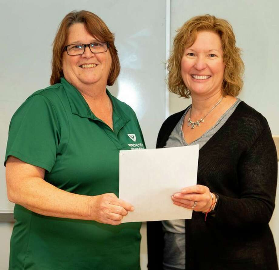 Dawn Yargeau, left, a supervisor of admissions and diversity at Wayne State University School of Medicine, and Heidi Lang, a pre-health professions adviser at Saginaw Valley State University, hold anEarly Assurance Program agreement that will provide SVSU pre-medicine students enhanced opportunities for admission to the WSU School of Medicine. (Photo provided)