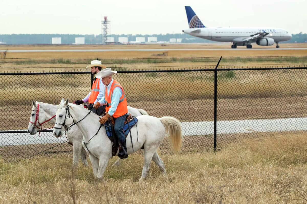 Airport Rangers Emil Sheegog and Leif Hakansson patrol along the perimeter fence at George Bush Intercontinental Airport on Monday, Dec. 17, 2018, in Houston. The Airport Rangers are mounted patrols that include off-duty law enforcement officers who ride their horses along the perimeter of the 13,000 acres of IAH including wooded trails.