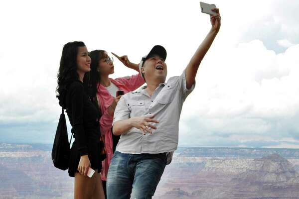 FILE - In this Aug. 2, 2015, file photo, tourists Joseph Lin, Ning Chao, center, and Linda Wang, left, pose for a selfie along the south rim at Grand Canyon National Park, Ariz. The Grand Canyon is celebrating 100 years as a national park in 2019. President Woodrow Wilson made the designation in 1919. But Teddy Roosevelt is credited for preserving the natural wonder as a game reserve and a national monument. (Emery Cowan/Arizona Daily Sun via AP, File)