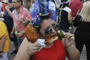 """Raquel Rother takes a bit of her """"chicken on a stick"""" as crowds fill Night in Old San Antonio (NIOSA) on its first night of celebrations during Fiesta Week on Tuesday, Apr. 24, 2018. Hosted by the San Antonio Conservation Society, thousands of eager party-goers flocked to La Villita for food, music and all-around revelry. Many came also went to NIOSA to see others who donned the ever-outlandish Fiesta hats as they strolled the grounds of La Villita. Proceeds from the event benefit the various projects by the conservation society."""