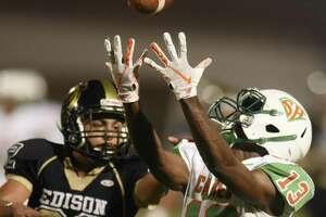 Brandon Adams of Sam Houston catches a first-half touchdown pass as Edison's Jason Balderas defends during high-school football action at Alamo Stadium on Thursday, Oct. 4, 2018.