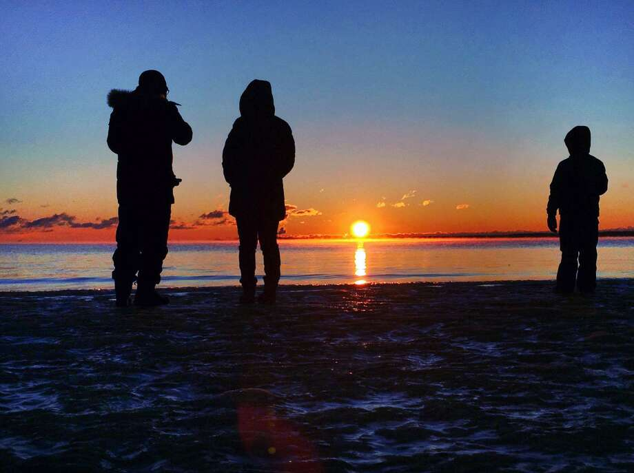 Onlookers witness the first sunrise of the year as the sun is seen above the horizon at 7:25 a.m. at Greenwich Point, Conn., Monday, Jan. 1, 2018. Photo: Bob Luckey Jr. / Hearst Connecticut Media / Greenwich Time