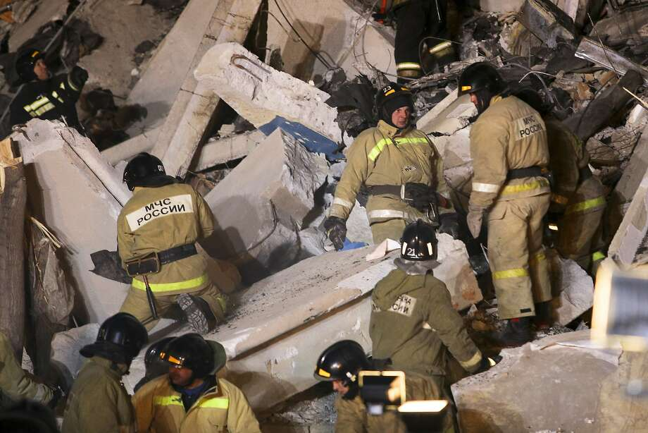 Emergency Situations employees working at the scene of a collapsed apartment building in Magnitogorsk, a city of 400,000 people, about 1,400 kilometers (870 miles) southeast of Moscow, Russia, Monday, Dec. 31, 2018. At least four people died Monday when part of a 10-story apartment building collapsed in Russia's Ural Mountains region, and hundreds of rescuers searched for survivors under the rubble in the frigid weather. (AP Photo/Maxim Shmakov) Photo: Maxim Shmakov, Associated Press