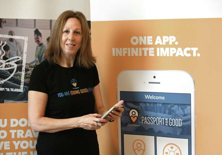 Gayle Farman has developed an app called Passport for Good that allows schools, businesses, individuals to keep track of their voluntarism at her offices Tuesday Nov. 20, 2018 in Troy, N.Y. (Skip Dickstein/Times Union)