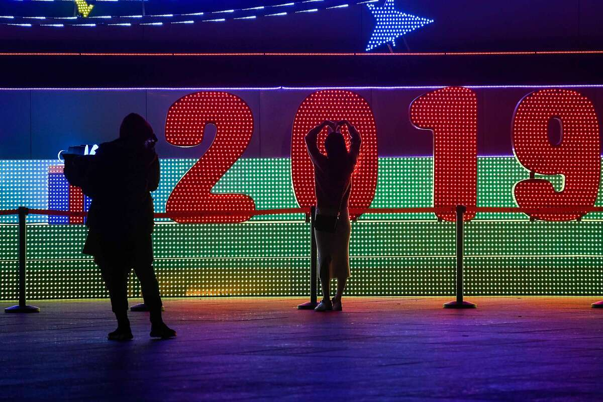 A woman poses for a photo during a New Year's Eve countdown event in front of Beijing's National Stadium, known as the Bird's Nest, in Beijing on December 31, 2018. (Photo by WANG ZHAO / AFP)WANG ZHAO/AFP/Getty Images