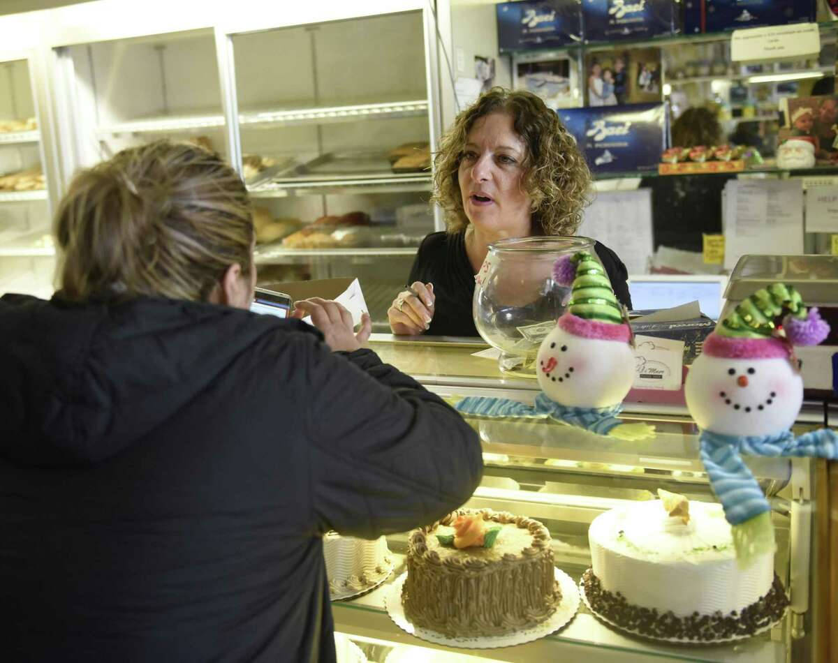 Owner Sabrina DiMare assists a customer at DiMare Pastry Shop in the Riverside section of Greenwich, Conn. Tuesday, Nov. 13, 2018.