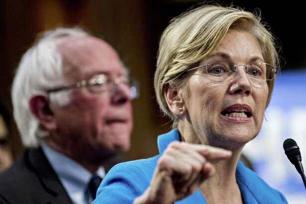 Sen. Elizabeth Warren, D-Mass., speaks as Sen. Bernie Sanders, I-Vt., listens during a news conference on Capitol Hill in Washington, D.C., on Sept. 13, 2017.