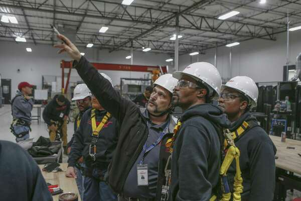 MIAT College of Technology Wind Turbine Instructor David Moriconi ( third from right ) talks to Anthony Snoddy ( second from right) before a ladder exercise Wednesday, Oct. 24, 2018, in Houston. MIAT College of Technology has a seven-month wind power technician career training program.