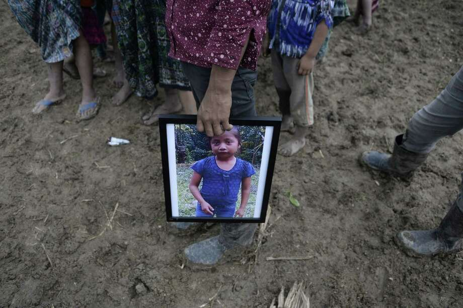 A person holds a picture of seven-year-old Jakelin Caal — who died in a Texas hospital two days after being taken into custody by US border patrol agents in a remote stretch of the New Mexico desert — during her funeral in the village of San Antonio Secortez, in Raxruha municipality, Alta Verapaz Department, 320 km north of Guatemala City, on Christmas Day. Photo: JOHAN ORDONEZ /AFP /Getty Images / AFP or licensors