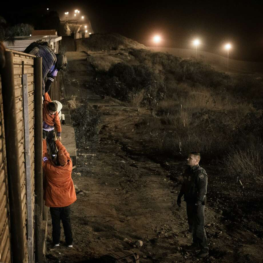 A migrant family from Honduras on Dec. 26 demonstrates the flaw of a border wall. People can climb over, here in the presence of the Border Patrol but just as easily outside its presence. Photo: Daniel Ochoa De Olza /Associated Press / Copyright 2018 The Associated Press. All rights reserved