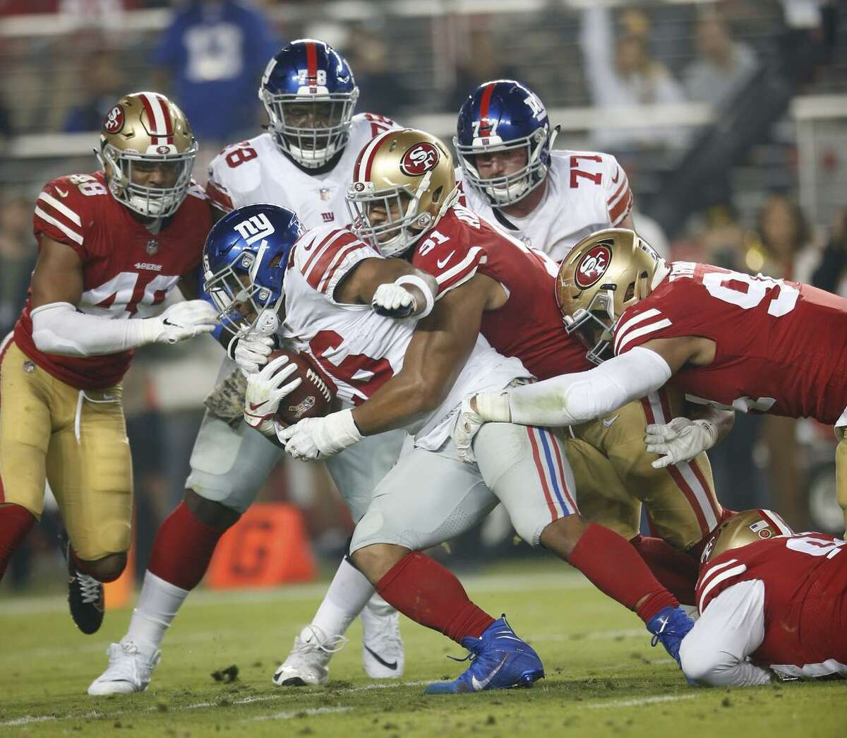 49ers defensive linemen Arik Armstead (91) and Solomon Thomas (right) tackle Giants rookie running back Saquon Barkley during a game at Levi's Stadium on Nov. 11. The defensive line is one area that general manager John Lynch says he'd like to improve.