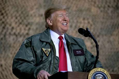 President Donald Trump speaks at a hangar rally at Al Asad Air Base, Iraq, Wednesday, Dec. 26, 2018. President Donald Trump, who is visiting Iraq, says he has 'no plans at all' to remove US troops from the country. (AP Photo/Andrew Harnik)