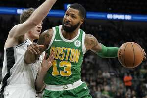 Boston Celtics' Marcus Morris (13) drives against San Antonio Spurs' Jakob Poeltl during the first half of an NBA basketball game, Monday, Dec. 31, 2018, in San Antonio. (AP Photo/Darren Abate)