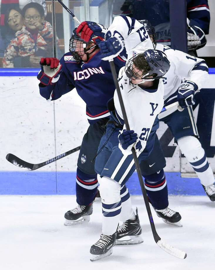 UConn's Adam Karashik, left, collides with Yale's Luke Stevens in the first period at Ingalls Rink on Monday. Photo: Arnold Gold / Hearst Connecticut Media / New Haven Register