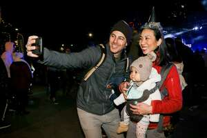 Michael Finelli takes a selfie with his wife, Rachael Nguyen and their nine-month-old daugther, Francine Nguyen-Finelli, while celebrating at the city's giant New Year's Eve party downtown at Hemisfair on Monday, Dec. 31, 2018.