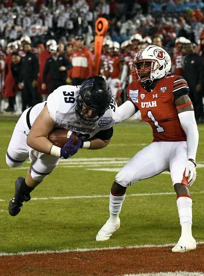 Northwestern's Trey Klock dives past Utah defensive back Jaylon Johnson for a TD. Photo: Denis Poroy / Associated Press