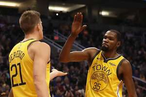 PHOENIX, ARIZONA - DECEMBER 31:  Kevin Durant #35 of the Golden State Warriors high fives Jonas Jerebko #21 afte scoring against the Phoenix Suns during the first half of the NBA game at Talking Stick Resort Arena on December 31, 2018 in Phoenix, Arizona. (Photo by Christian Petersen/Getty Images)