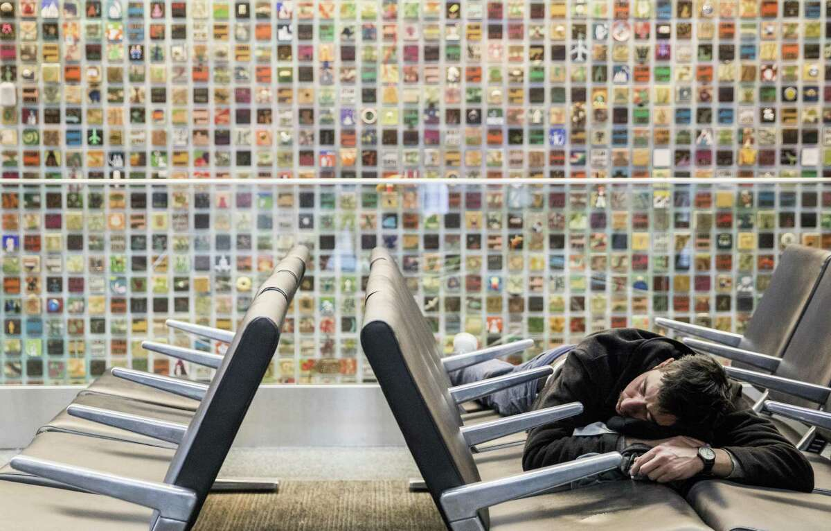A man takes a nap on a row of seats in the ticketing area of San Francisco International Airport on Wednesday, Dec. 19, 2018.