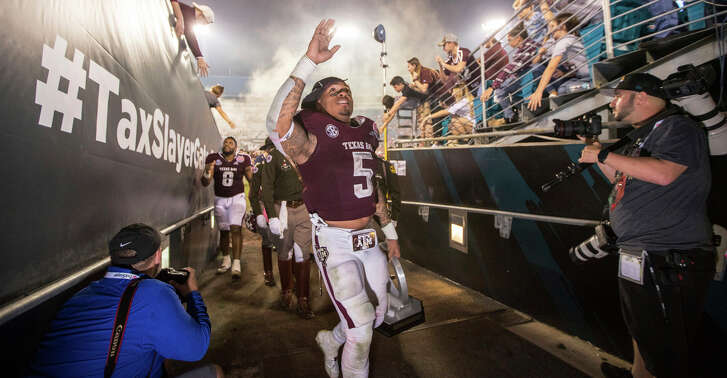 Texas A&M running back Trayveon Williams (5) , holding his MVP award, waves to the crowd as he heads into the locker room after the Gator Bowl NCAA college football game against North Carolina State on Monday, Dec. 31, 2018, in Jacksonville, Fla. (James Gilbert/The Florida Times-Union via AP)