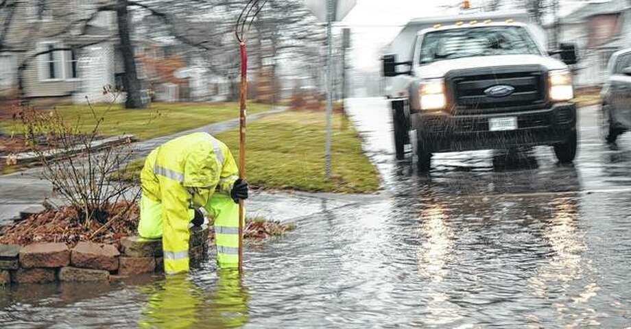 A Jacksonville street department worker tries to clear a storm drain as water pools from Monday's heavy rains. Photo: Audrey Clayton | Journal-Courier