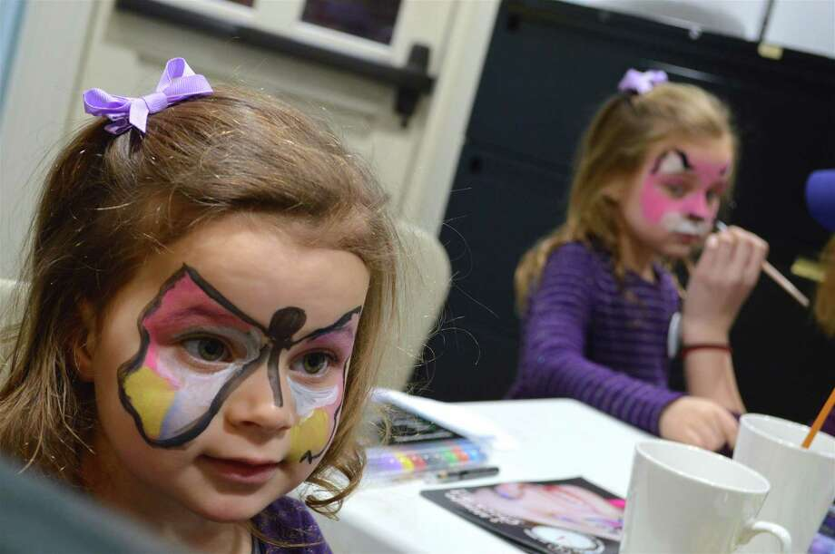 Kate Taylor, 3, of Westport, left, and her sister, Emma, 5, get face painting at the First Light Festival at the Westport Historical Society, Monday, Dec. 31, 2018, in Westport, Conn. Photo: Jarret Liotta / For Hearst Connecticut Media / Westport News Freelance