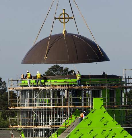 The steeple for Sacred Heart Catholic Church's new 1,500 seat sanctuary and chapel rises into place, Wednesday, April 4, 2018, in Conroe. The parish, which celebrated its 100th anniversary in 2016, is scheduled to open its new buildings in Octomber 2018.