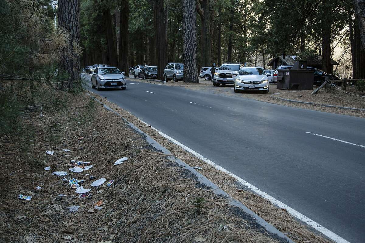 In this Monday, Dec. 31, 2018 photo provided by Dakota Snider shows a road lined with trash in Yosemite National Park, Calif. Human feces, overflowing garbage, illegal off-roading and other damaging behavior in fragile areas were beginning to overwhelm some of the West's iconic national parks on Monday, as a partial government shutdown left the areas open to visitors but with little staff on duty. (Dakota Snider via AP)