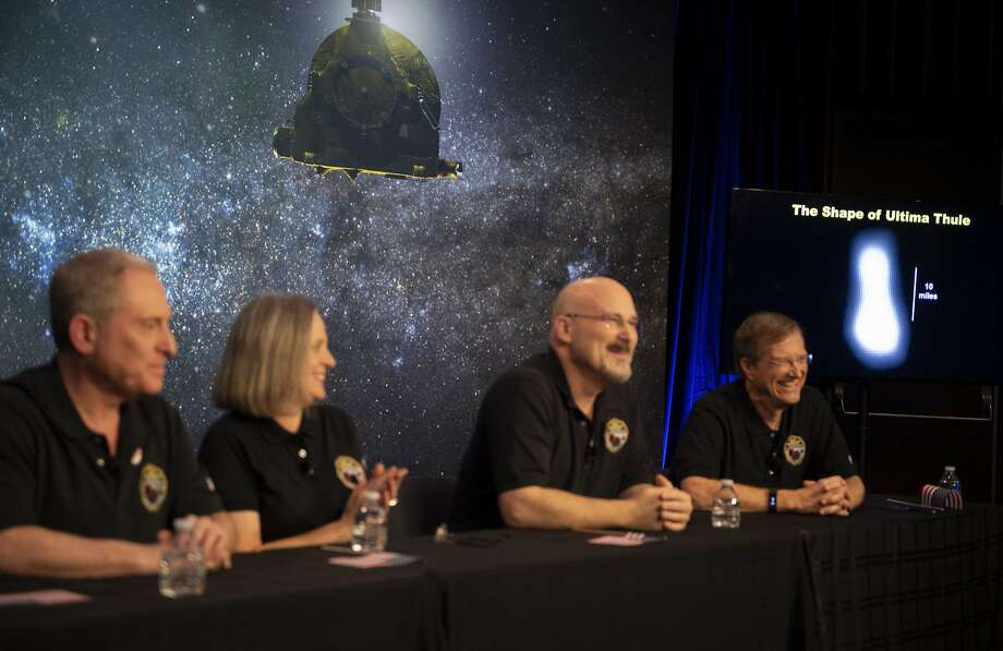 NASA scientists display an image of Ultima Thule (right) — a tiny, icy object 4 billion miles away — after a spacecraft completed a flyby of the body, shaped like a bowling pin. Photo: Joel Kowsky / Associated Press
