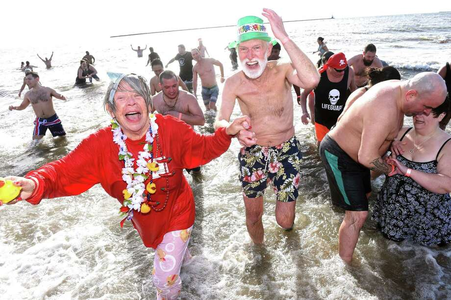 Liz Duckrow (left) and her husband, Brad (center), of New Haven emerge from the Long Island Sound during the 17th annual Plunge for Parks fundraiser at Lighthouse Point Park in New Haven on January 1, 2019. Photo: Arnold Gold / Hearst Connecticut Media / New Haven Register