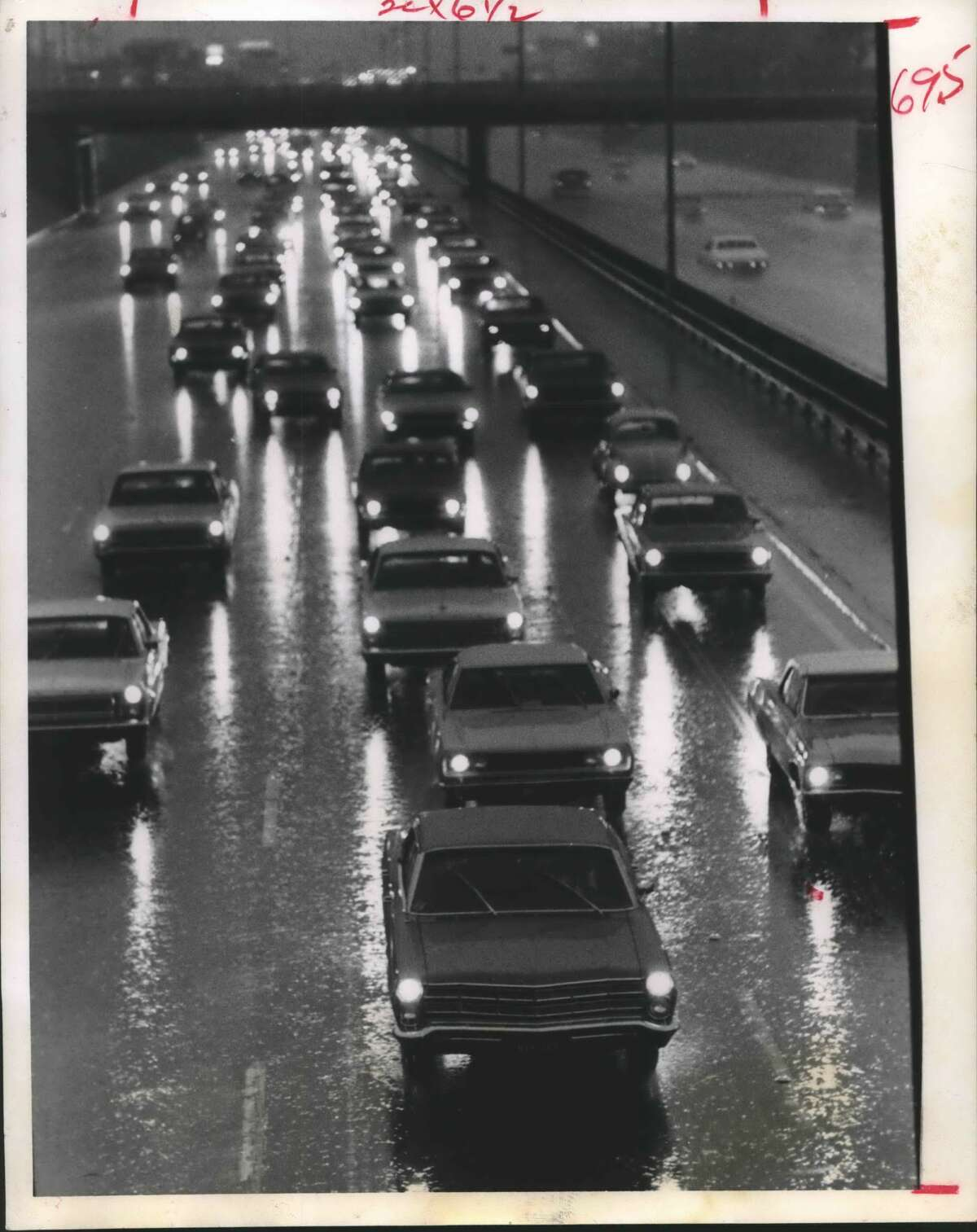 JanuaryHouston traffic moves during a heavy fog event. Only two major and thirteen minor accidents, normal for the period, were reported during the rush hours. Police praised to motorists for carefully driving. Traffic is shown moving slowly on the Southwest Freeway.
