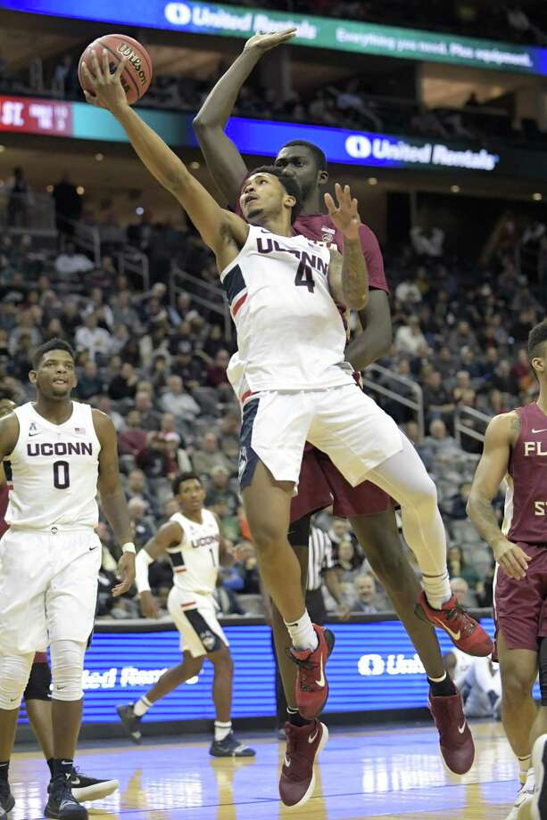 UConn guard Jalen Adams puts up a shot as Florida State center Christ Koumadje defends on Dec. 8. Photo: Bill Kostroun / Associated Press / Copyright 2018 The Associated Press. All rights reserved
