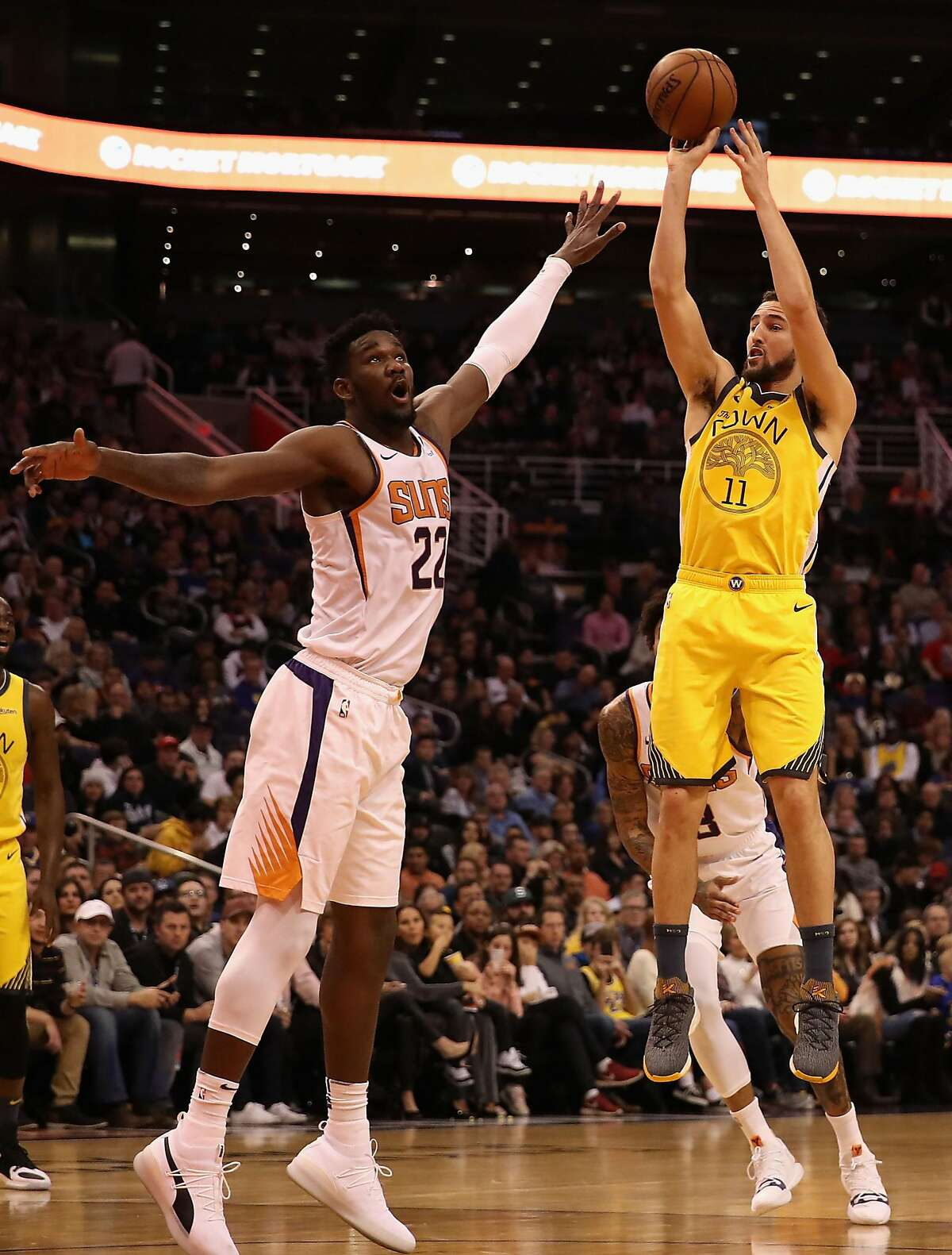 PHOENIX, ARIZONA - DECEMBER 31: Klay Thompson #11 of the Golden State Warriors puts up a shot over Deandre Ayton #22 of the Phoenix Suns during the first half of the NBA game at Talking Stick Resort Arena on December 31, 2018 in Phoenix, Arizona. The Warriors defeated the Suns 132-109. (Photo by Christian Petersen/Getty Images)