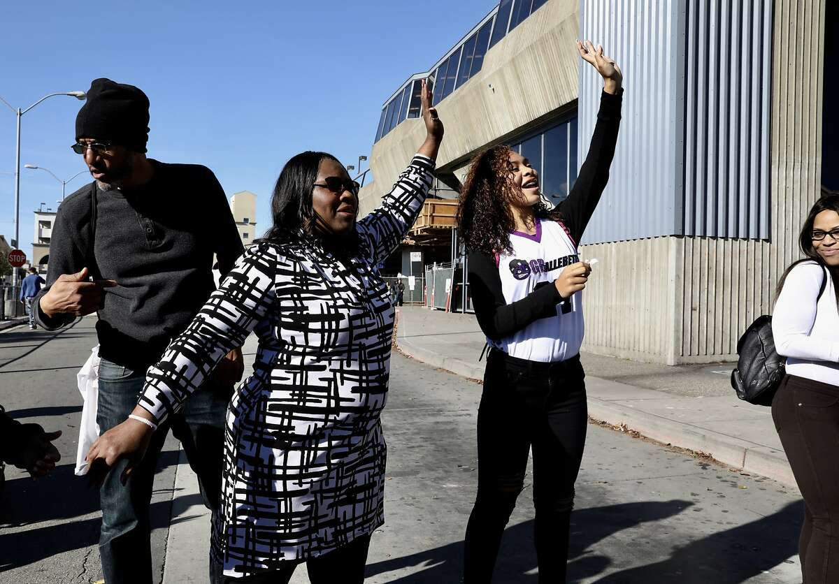 Wanda Johnson (left) and her granddaughter, Tatiana Grant, wave to a speaker on stage at the BART Fruitvale Station during a vigil on the 10 year anniversary of Oscar Grant's death in Oakland, Calif., on Tuesday, January 1, 2019. Grant was fatally shot by a BART police officer during the early hours of New Year's Day a decade ago.