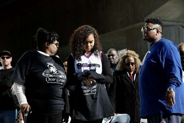 Tatiana Grant (center), daughter of Oscar Grant III, prays at the BART Fruitvale Station during a vigil on the 10 year anniversary of Grant's death in Oakland, Calif., on Tuesday, January 1, 2019. Grant III, 22, was fatally shot by a BART police officer during the early hours of New Year's Day a decade ago.